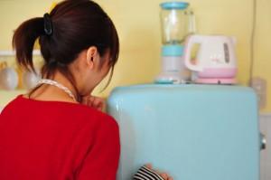 冷蔵庫をしめる女性