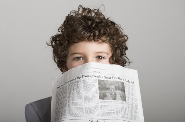 新聞を持つ子ども